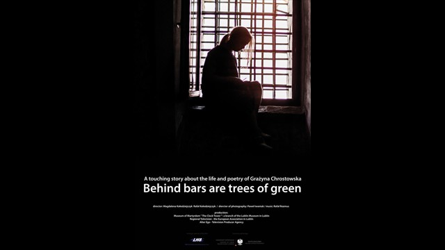 Behind bars are trees of green